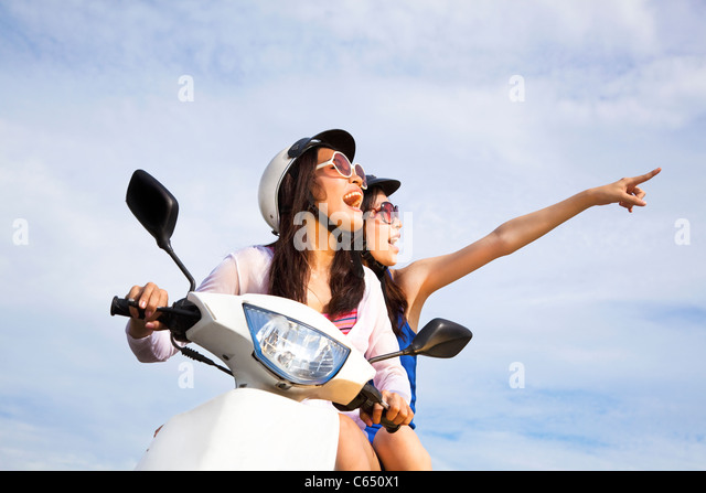 happy girls riding scooter enjoy summer vacation - Stock Image