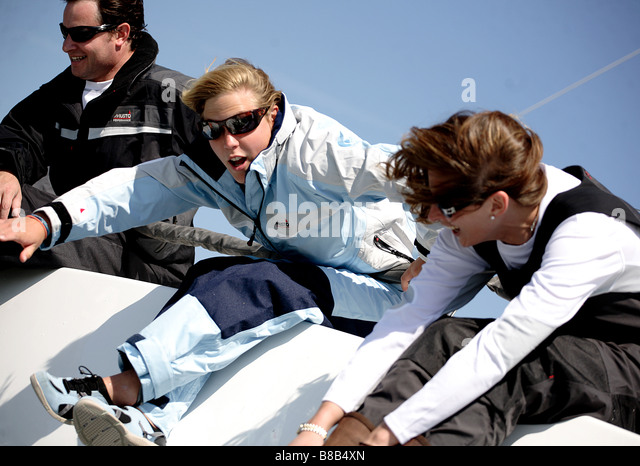 3 adults,2 woman and 1 man leaning over the edge of a yacht while racing. The picture is color in a landscape format. - Stock Image