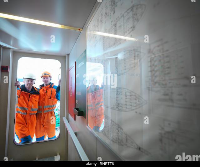 Sailors looking through doorway on deck - Stock Image