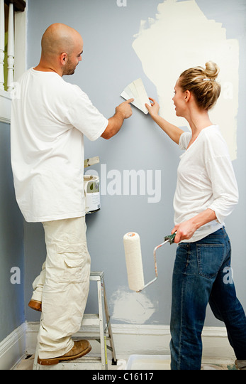 Couple painting wall, woman holding color swatch - Stock Image