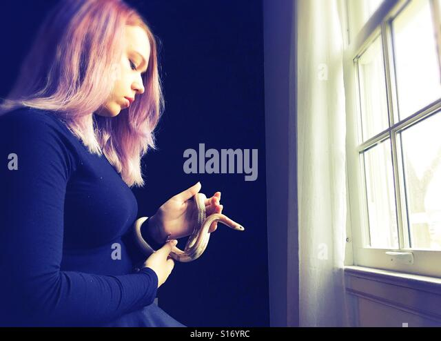 A teenage girl holding a snake next to a window. - Stock Image