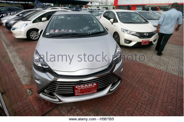 A man walks past Hybrid cars for sale in Colombo October 24, 2014. REUTERS/Dinuka Liyanawatte (SRI LANKA - Tags: - Stock Image