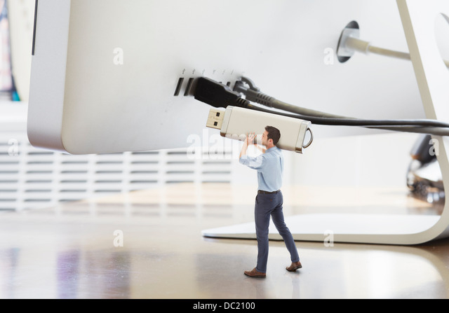 Businessman holding large USB stick next to oversized computer monitor - Stock Image
