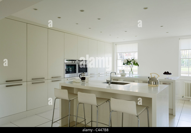 White contemporary kitchen with Corian worktops, barstools and fitted cupboards - Stock-Bilder