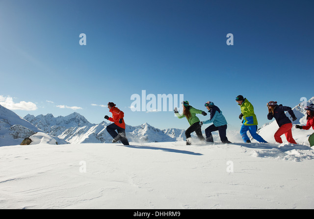 Friends running in snow, Kuhtai, Austria - Stock Image