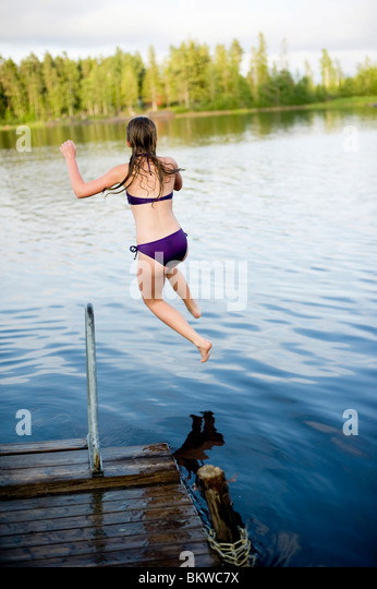 Closeup on girl jumping into the water - Stock Image