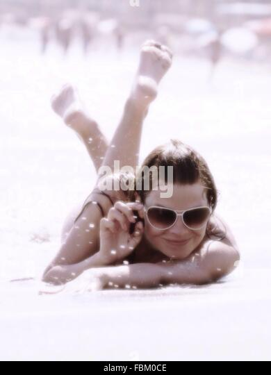 Portrait Of A Happy Young Woman Lying On Beach - Stock Image