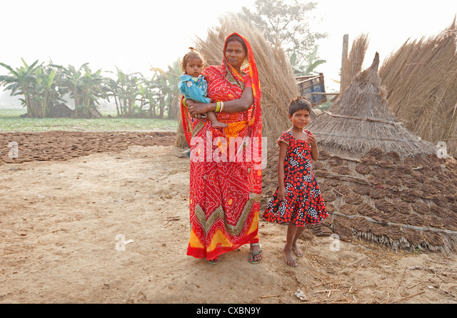 Mother in red sari and her two children in rural Bihari village at dawn, Sonepur, Bihar, India, Asia - Stock Image