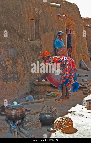 Village woman, Larabanga, Ghana, cooking on open fire in the traditional way outside her house built of mud. - Stock Image
