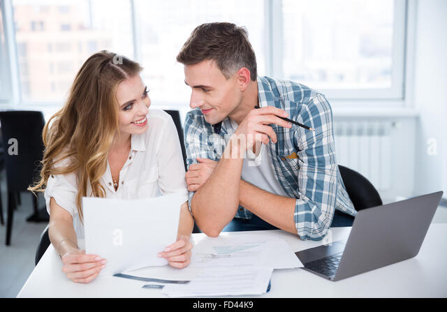 Cheerful man and woman working and flirting on business meeting - Stock Image