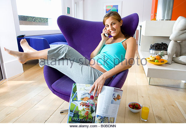 Young pregnant woman with magazine in armchair, using telephone, smiling, portrait - Stock Image