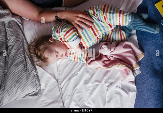Cropped image of woman touching baby girl on bed - Stock-Bilder