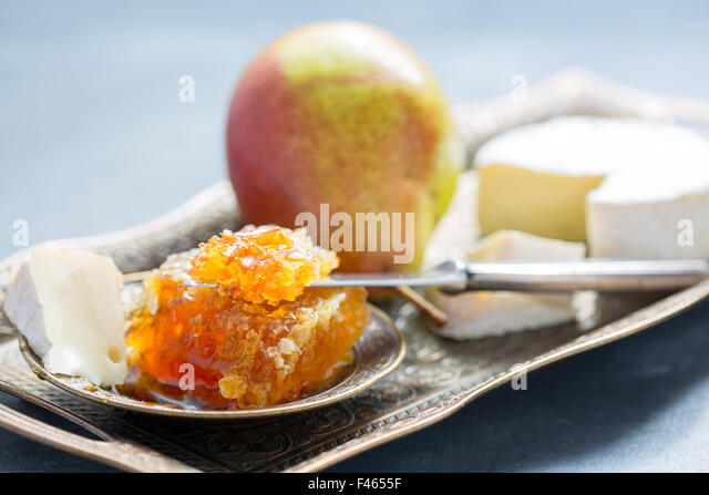 Honey comb, ripe pear and brie. - Stock Image