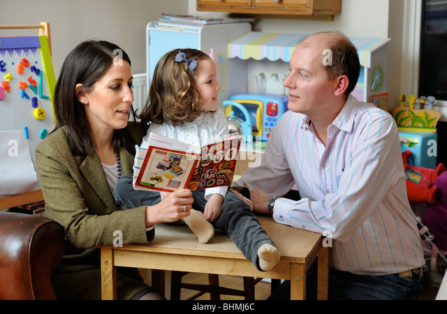 A young couple with their daughter in a nursery playroom UK - Stock Image