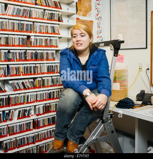 Woman sitting on ladder in stockroom - Stock-Bilder