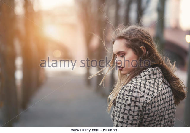 Young woman looking down in a windy park - Stock Image