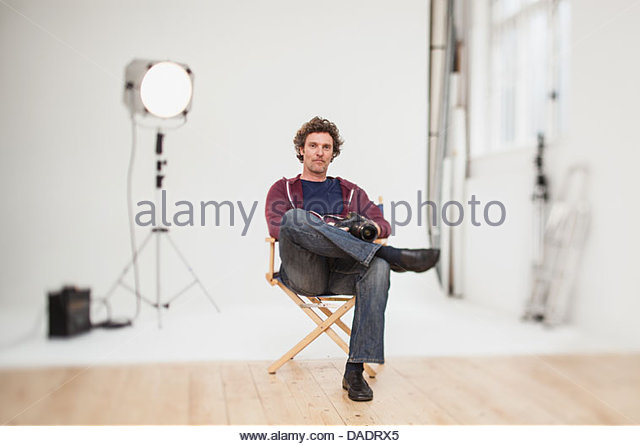 Portrait of photographer sitting in directors chair - Stock Image