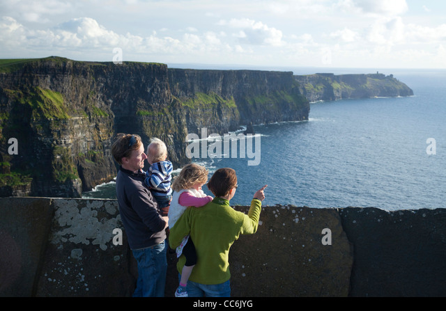 Family enjoying the view at the Cliffs of Moher, The Burren, County Clare, Ireland. - Stock Image