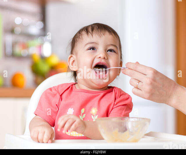 smiling baby eating food on kitchen - Stock Image