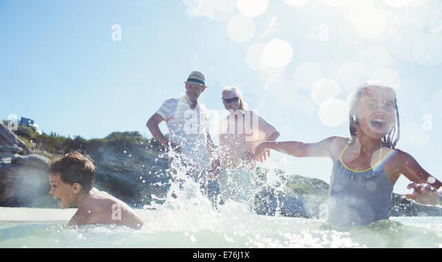 Family splashing each other on beach - Stock-Bilder