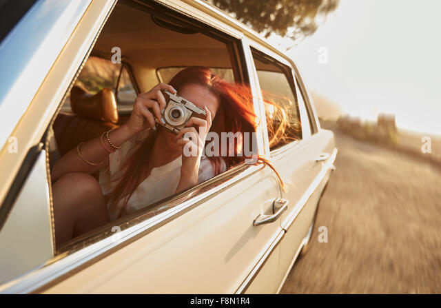 Shot of  young woman taking photos while sitting in a car. Female capturing a perfect road trip moment. - Stock-Bilder