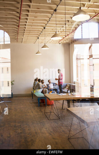Creative businessman leading meeting in open office - Stock Image