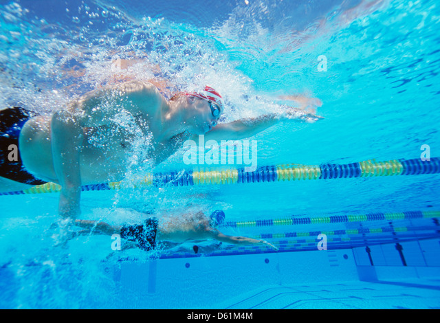 Underwater shot of three male thletes in swimming competition - Stock Image
