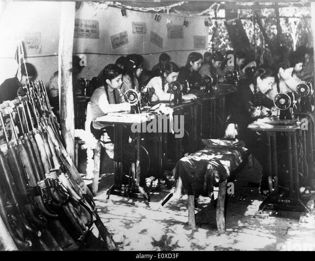 Workers making uniforms during Vietnam War - Stock Image