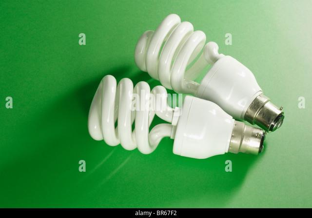 Energy saving light bulbs on green background - Stock Image