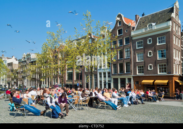 Crowds enjoying a drink in a cafe by the Singel canal central Amsterdam Netherlands Holland EU Europe - Stock Image