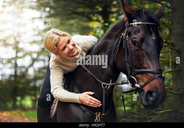Portrait of a woman patting her horse while in saddle - Stock Image