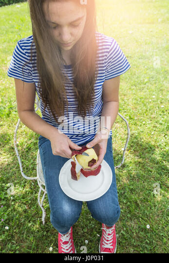 Young woman peeling an apple in the garden - Stock Image