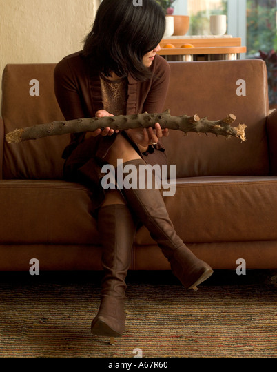 Oriental Woman  Sat On Sofa Holding Branch - Stock Image