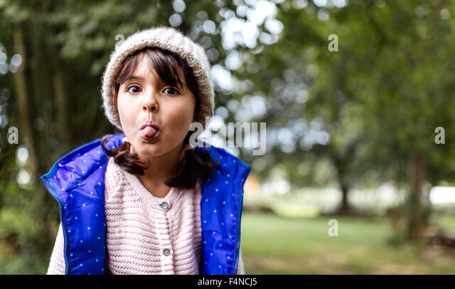 Portrait of little girl sticking out her tongue - Stock Image