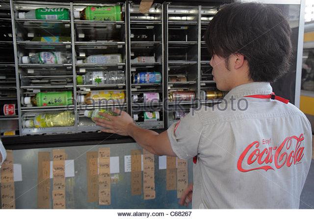 Tokyo Japan Ryogoku JR Ryogoku Station platform Coca-Cola employee Asian man stocking filling drink vending machine - Stock Image
