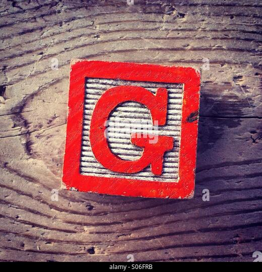 It's a woodblock toy with an alphabet letter on it: G - Stock Image