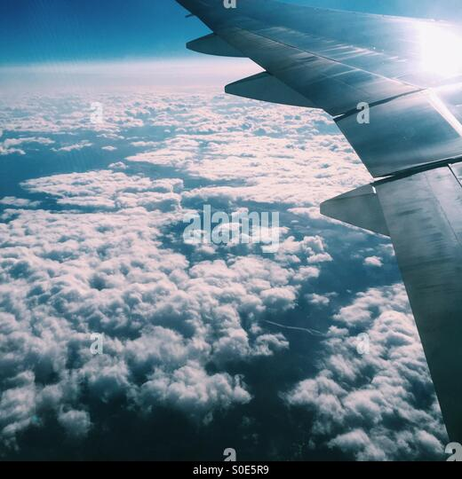 Aerial view of airplane wing and clouds as seen from window of airplane. - Stock Image