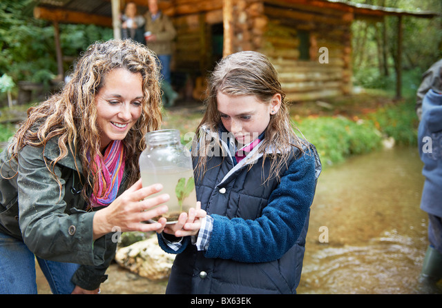 Mom and daughter examining insect in jar - Stock Image