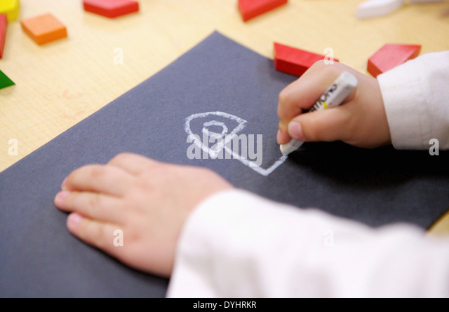 Young Child Drawing with Crayon on Black paper - Stock Image