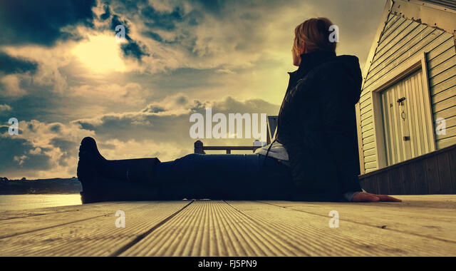 young woman sitting comfortably on wooden beach cabin floor - Stock-Bilder