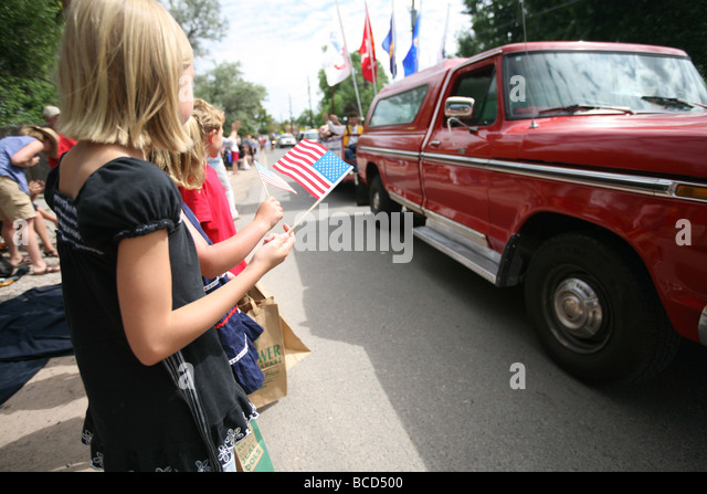 Children holding US flag at 4th of July parade - Stock-Bilder
