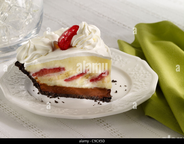 Strawberry Banana Cream Pie with Whip Cream and a strawberry on a white plate - Stock Image