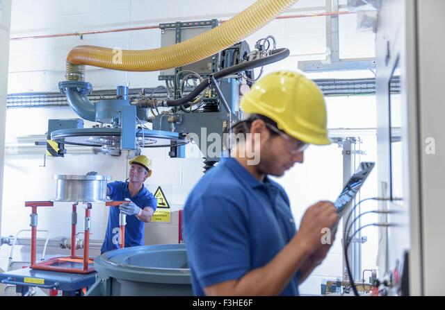 Workers operating environmental testing equipment with digital tablet in electronics factory - Stock Image