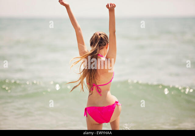 Teenage girl jumping up in the air on the beach - Stock Image