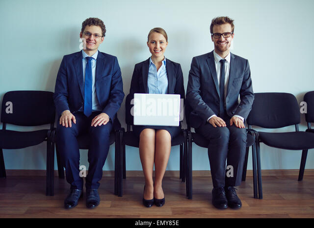 Happy co-workers sitting on chairs along wall - Stock Image