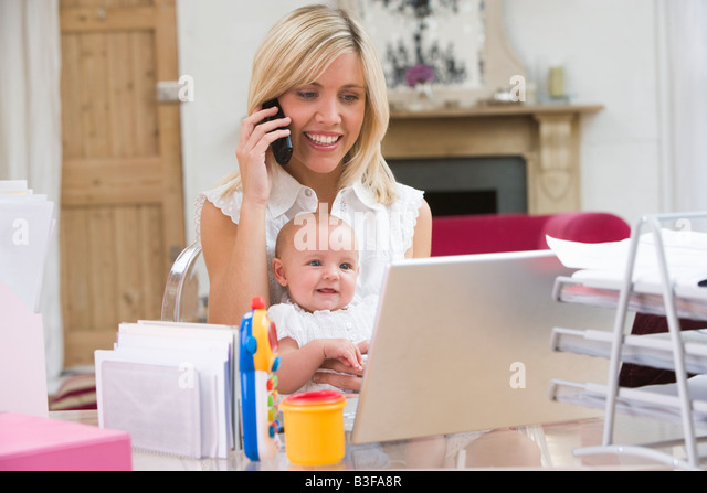 Mother and baby in home office with laptop and telephone - Stock Image