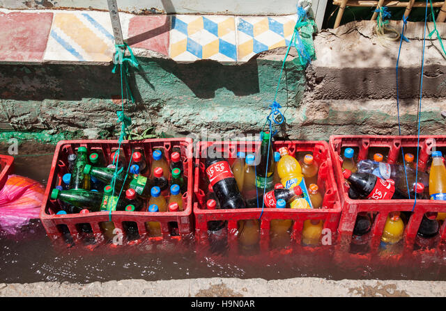 Cooling soft drinks in a water channel. - Stock Image