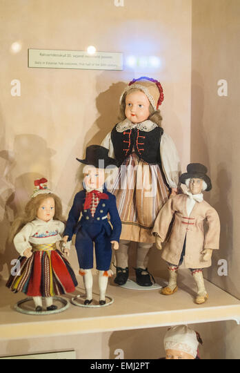 Toy dolls in toy museum in Tartu in Estonia, dressed in traditional Estonian costumes and dresses. Woman and children. - Stock Image