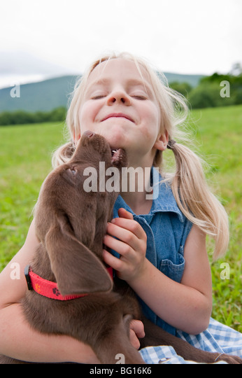 Young girl hugging her puppy - Stock-Bilder