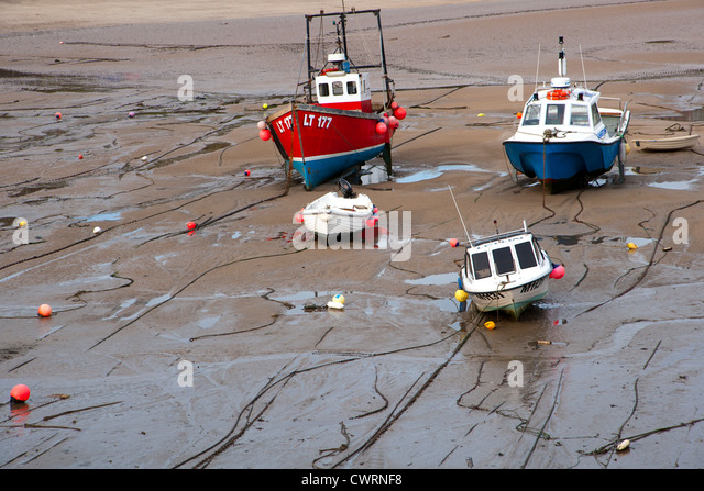 Boats beached at low tide in Tenby Harbour, Pembrokeshire, Wales, UK - Stock Image